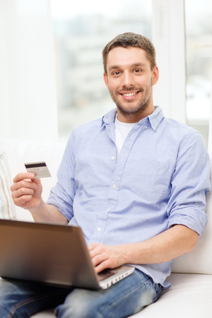 latin man: technology, home and lifestyle concept - smiling man working with laptop and credit card at home