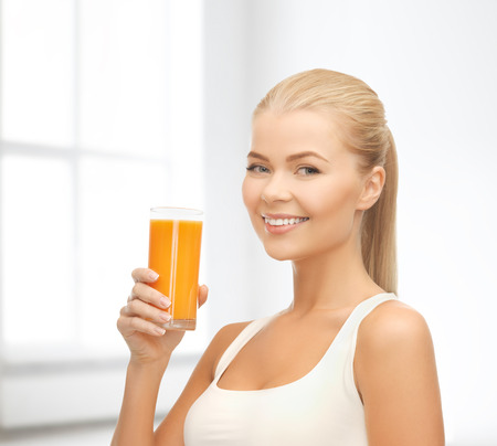 food, healthcare and diet concept - smiling young woman holding glass of orange juice photo