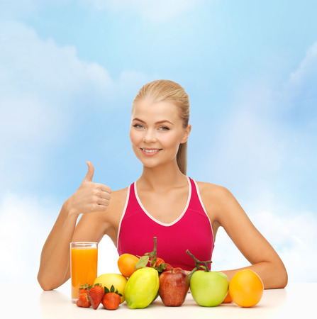 fitness, healthcare and diet concept - smiling woman with organic food or fruits on table photo