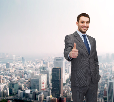 thumbs up sign: business, gesture and office concept - handsome buisnessman showing thumbs up Stock Photo
