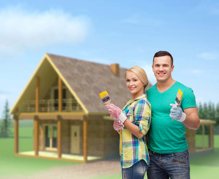 repair, construction and maintenance concept - smiling couple with paintbrush photo