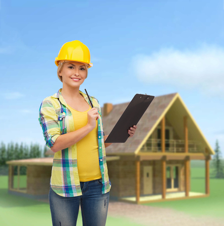 repair, construction and maintenance concept - smiling woman in helmet with clipboard photo