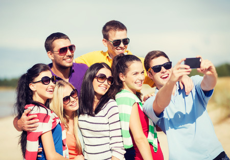 summer, holidays, vacation, happy people concept - group of friends taking picture with smartphone photo