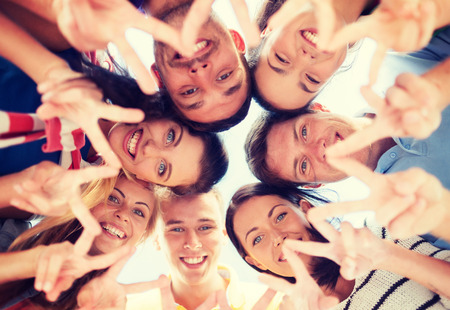 making fun: summer, holidays, vacation, happy people concept - group of teenagers looking down and showing finger five gesture