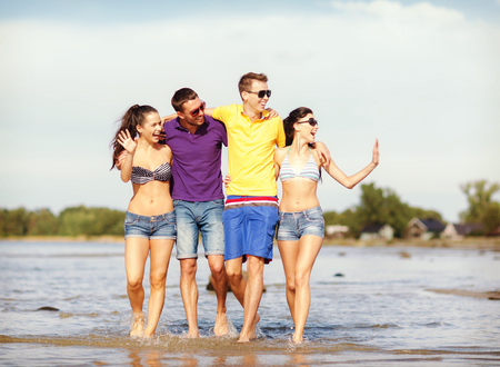 summer, holidays, vacation, happy people concept - group of friends having fun on the beach photo