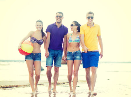 summer, holidays, vacation, happy people concept - group of friends having fun playing with ball on the beach photo