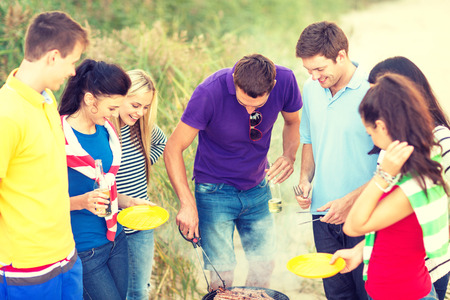 barbecue party: summer, holidays, vacation, happy people concept - group of friends having picnic and making barbecue on the beach