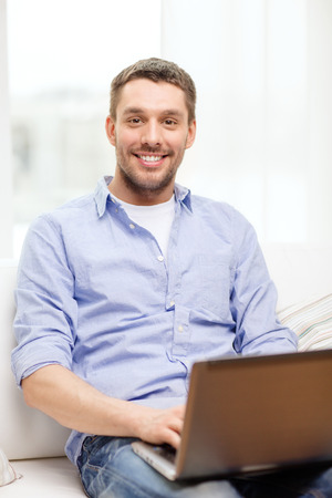 technology, home and lifestyle concept - smiling man working with laptop at home photo