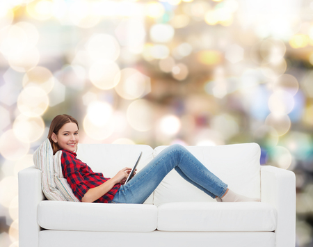 technology and happy people concept - teenage girl sitting on sofa with tablet pc photo