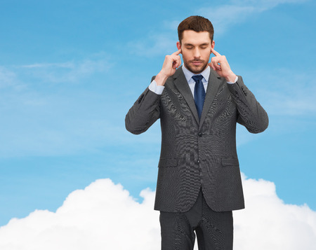 business concept - annoyed businessman covering ears with his hands photo
