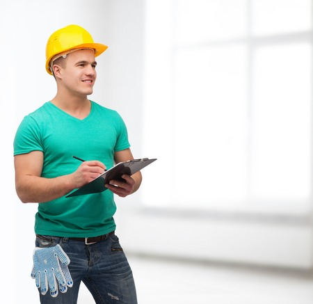 making notes: repair, construction and maintenance concept - smiling man in helmet with clipboard