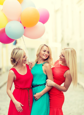 celebration and happy people concept - beautiful girls with colorful balloons in the city photo