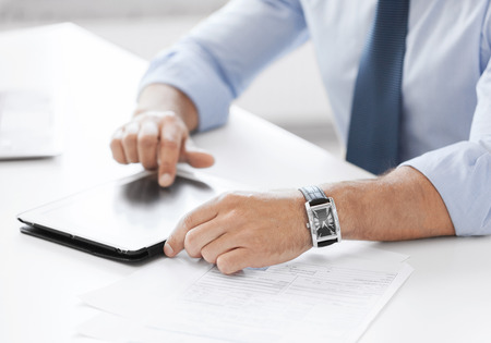 business, technology and office concept - businessman with tablet pc in office photo