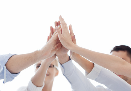 team winner: success and winning concept - happy business team giving high five in office