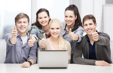 scholar: education, technology and internet concept - smiling students with laptop showing thumbs up at school Stock Photo
