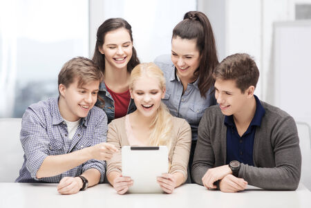 education, technology and internet concept - smiling students with tablet pc at school photo