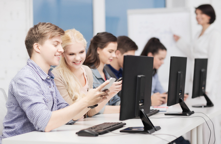 education, technology and internet concept - students with computer monitor and smartphones photo