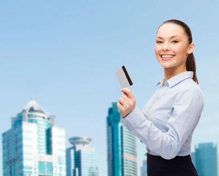 business and bank concept - smiling businesswoman showing credit card photo