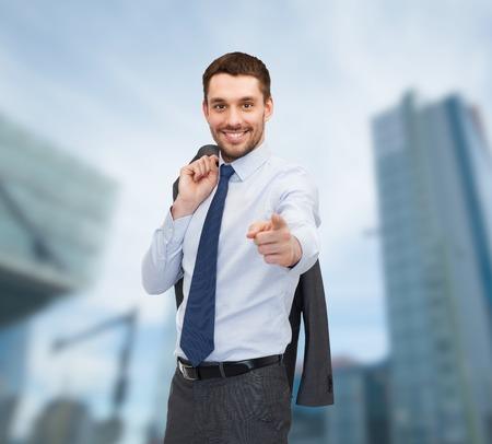 invitando: concepto de negocios y oficina - buisnessman guapo con chaqueta sobre el hombro que señala el dedo en usted