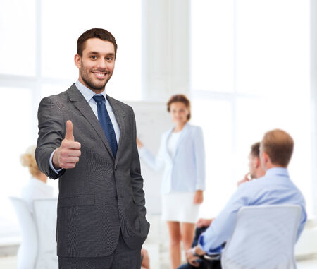 business, gesture and office concept - handsome buisnessman showing thumbs up in office photo