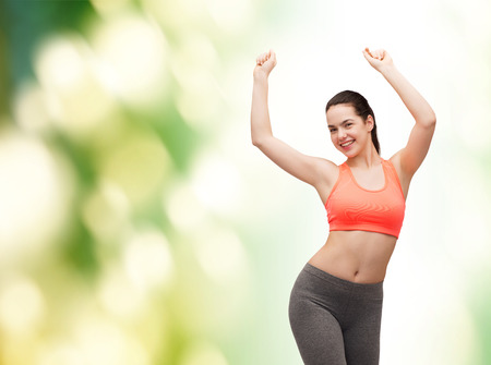 fitness and diet concept - smiling teenage girl in sportswear dancing photo