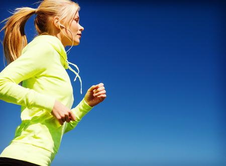 escuchando musica: deporte y estilo de vida concepto - mujer haciendo correr con auriculares al aire libre Foto de archivo