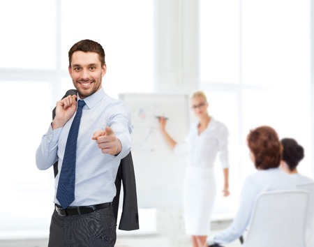 business and office concept - handsome buisnessman with jacket over shoulder pointing finger at you photo