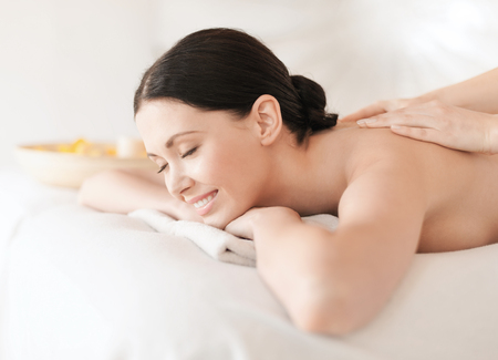 health and beauty, resort and relaxation concept - woman in spa salon getting massage photo