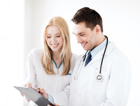 healthcare and medical concept - two doctors writing prescription photo