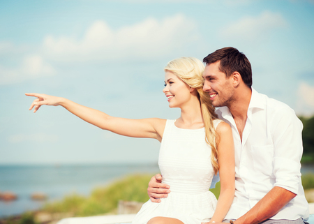 summer holidays and dating concept - couple sitting at sea side photo