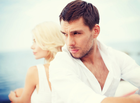 summer holidays, dating and relationships concept - stressed man with woman outside photo