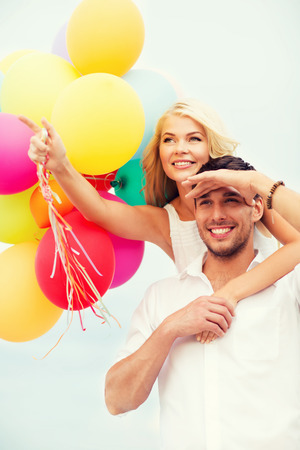 anniversary beach: summer holidays, celebration and dating concept - couple with colorful balloons at seaside