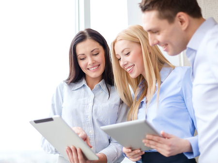 business and office concept - smiling business team working with tablet pcs in office photo