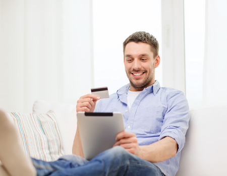people buying: technology, home and lifestyle concept - smiling man working with tablet pc computer and credit card at home