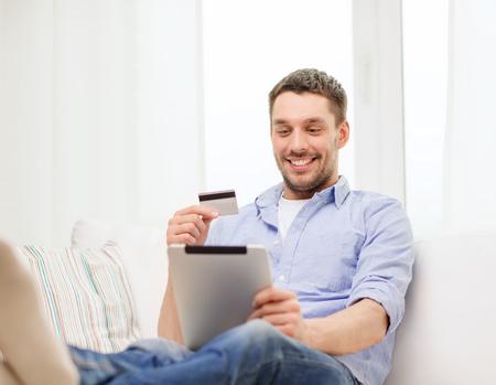 personas mirando: tecnolog�a, hogar y estilo de vida concepto - hombre sonriente de trabajo con la tableta de la computadora de la PC y la tarjeta de cr�dito en casa Foto de archivo