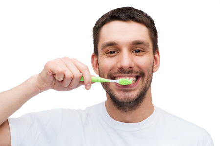 brushing teeth: health and beauty concept - smiling young man with toothbrush
