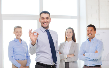 young executives: office, business, and teamwork concept - friendly young smiling businessman with team on back showing ok-sign