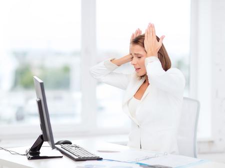 dolor de cabeza: negocio, oficina, la escuela y la educación concepto - destacó la empresaria con el ordenador en el trabajo Foto de archivo