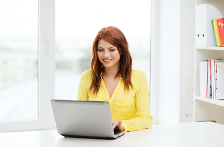 education, e-learning and technology concept - smiling student with laptop computer at school