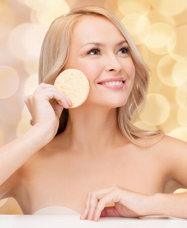 health, beauty and spa concept - beautiful woman with sponge photo