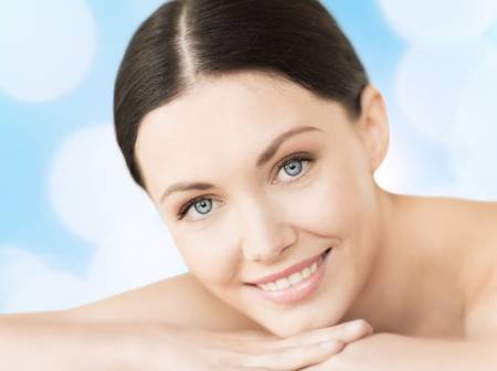 spa, resort and vacation concept - smiling woman in spa salon lying on the massage desk photo