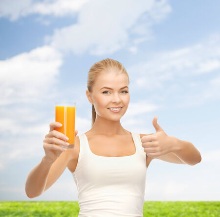 food, diet and healthcare concept - smiling woman holding glass of orange juice and showing thumbs up photo