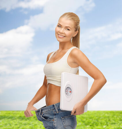 fat burning: fitness, diet and healthcare concept - sporty woman showing big pants and holding scales