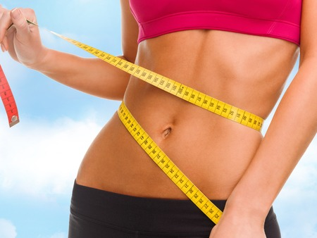 sport, fitness and diet concept - close up of trained belly with measuring tape photo