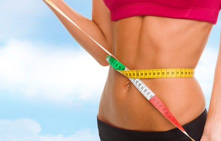 woman measuring waist: sport, fitness and diet concept - close up of trained belly with measuring tape