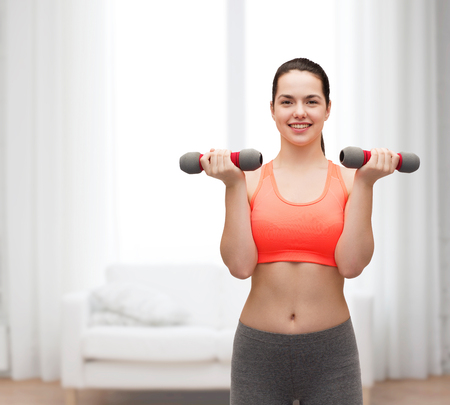 pumping: sport, exercising and healthcare concept - young sporty woman with light dumbbells Stock Photo