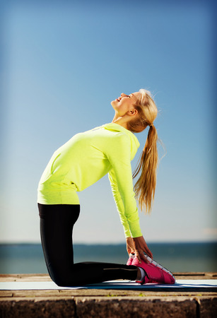 back exercise: sport and lifestyle concept - woman doing sports outdoors Stock Photo