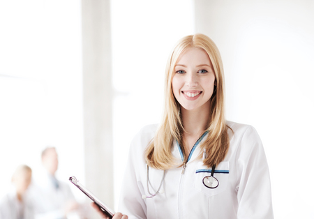 cardiologist: healthcare and medical concept - female doctor with stethoscope writing prescription