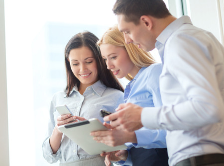 young professionals: business and office concept - smiling business team working with tablet pcs and smartphones in office Stock Photo