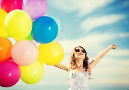 Sommerferien, Feier, Familie, Kinder und Menschen Konzept - glückliches Mädchen mit bunten Luftballons